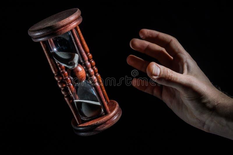 Las manos humanas quieren coger el tiempo en el reloj de arena aislado en fondo negro fotografía de archivo