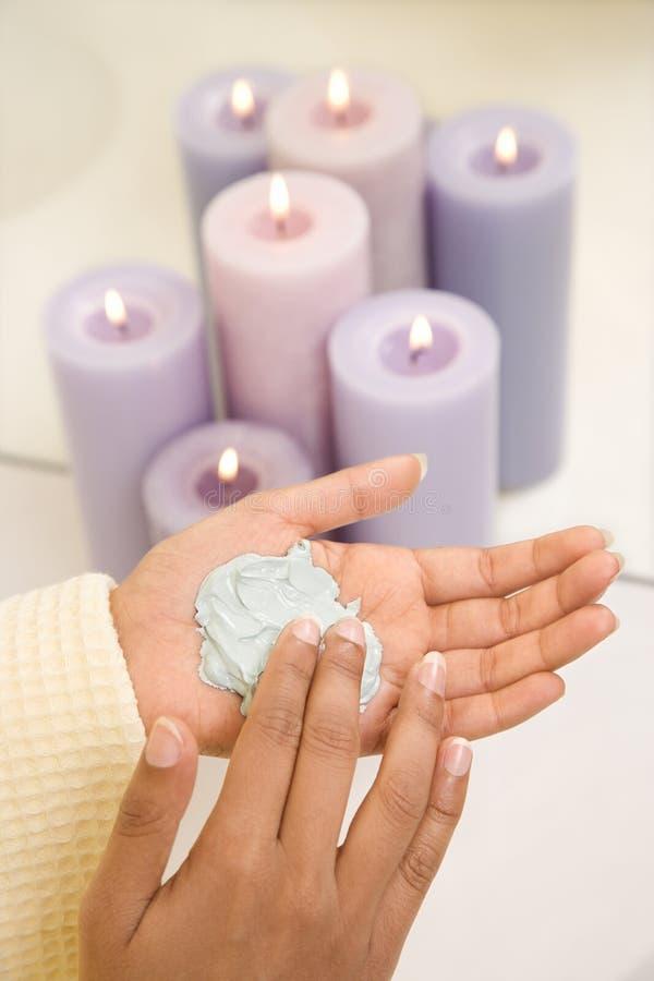 Las manos jovenes de los womans con el facial friegan. imágenes de archivo libres de regalías