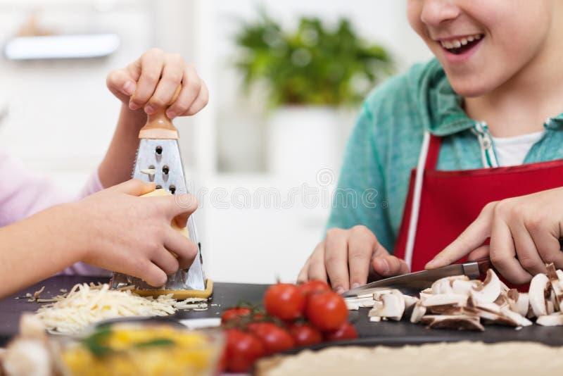 Las manos jovenes del adolescente preparan una pizza en la cocina - cercana para arriba foto de archivo
