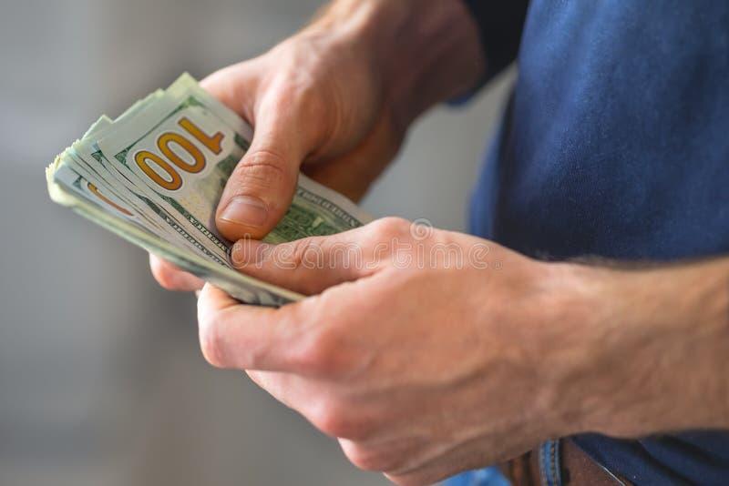 Las manos masculinas con los billetes de banco se cierran para arriba foto de archivo