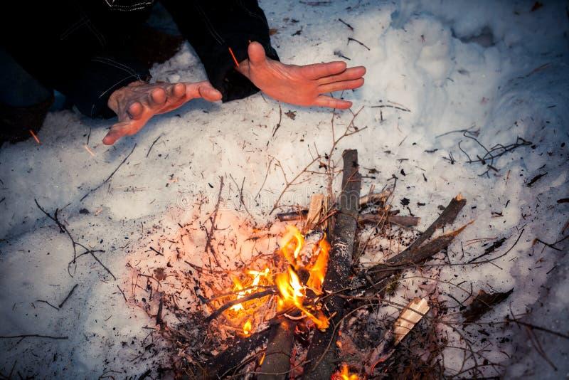 Las manos masculinas congeladas se están calentando sobre hoguera en la noche del invierno fotografía de archivo