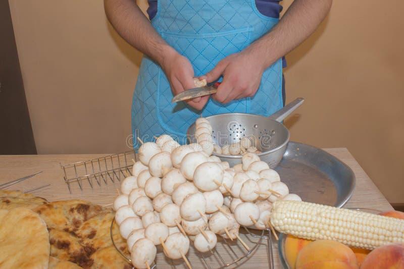 Las manos masculinas cortan la seta con el cuchillo, delantal en fondo Concepto del proceso de cocinar Verduras del corte del uni fotos de archivo libres de regalías