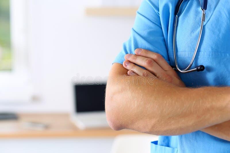 Las manos masculinas del doctor del terapeuta de la medicina cruzaron en su pecho adentro imagen de archivo libre de regalías