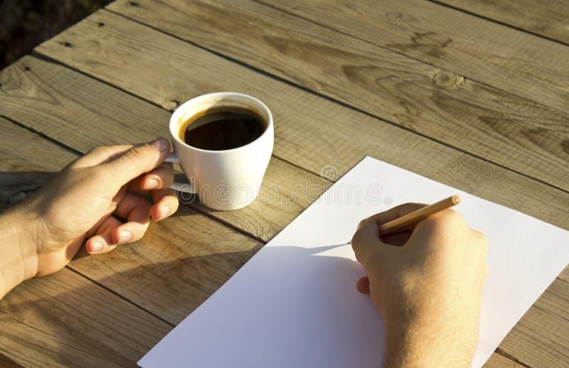 Las manos masculinas están sosteniendo la taza de café y están escribiendo en el papel en blanco fotografía de archivo libre de regalías