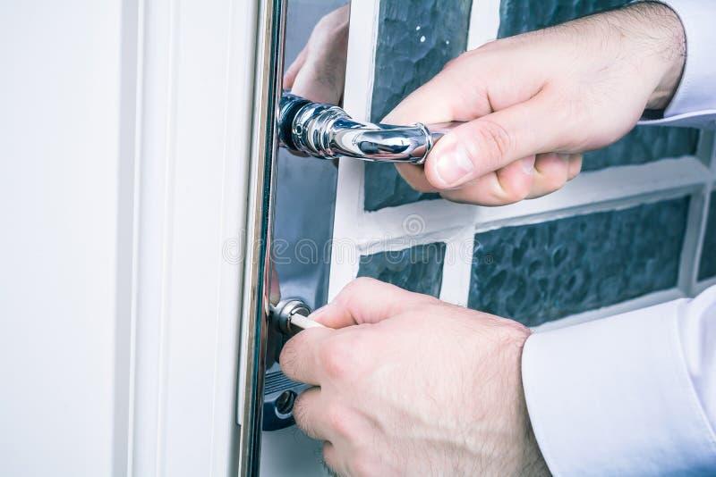 Las manos masculinas que sostienen el tirador de puerta y que cierran la puerta con una llave, previenen concepto del robo imagen de archivo