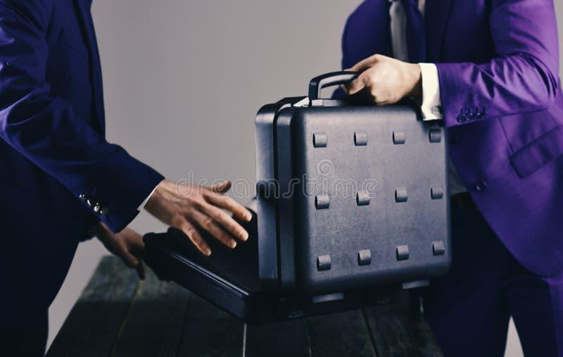 Las manos masculinas sostienen la cartera negra abierta en la tabla de madera imágenes de archivo libres de regalías