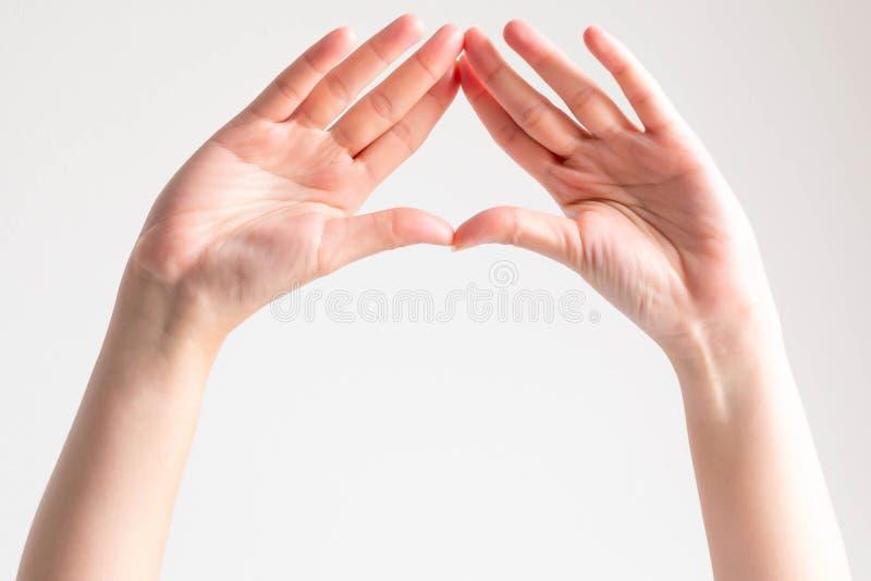 Las manos muestran las palmas y las yemas del dedo del empalme juntas para ser marco del triángulo foto de archivo