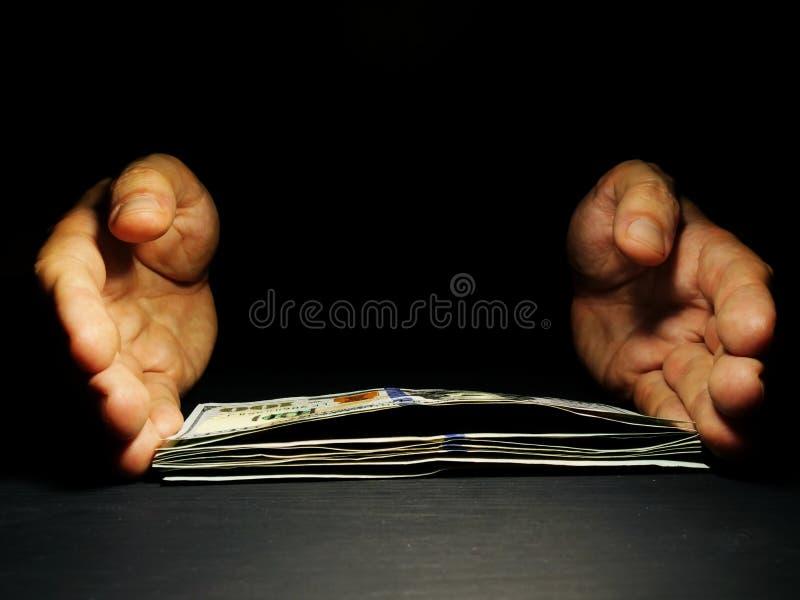 Las manos ofrecen el dinero en el espacio libre oscuro Préstamos y préstamo imagenes de archivo