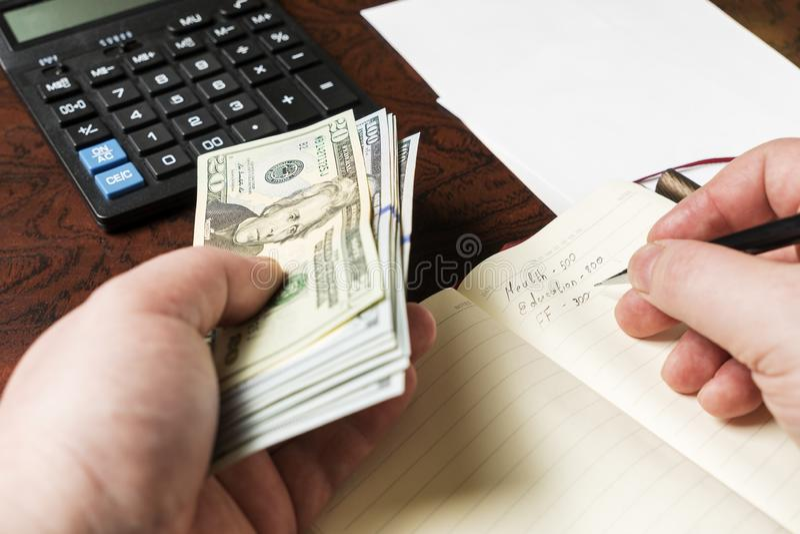 Las manos para hombre están llevando a cabo dólares y están contando costos en la calculadora fotos de archivo libres de regalías