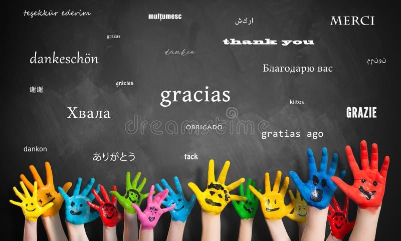 Las manos pintadas de los niños delante de una pizarra con el mensaje 'le agradecen 'en muchas idiomas imágenes de archivo libres de regalías