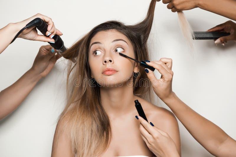 Las manos que hacen el peinado y componen a la muchacha desnuda hermosa joven imágenes de archivo libres de regalías
