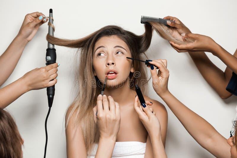 Las manos que hacen el peinado y componen a la muchacha desnuda hermosa joven foto de archivo