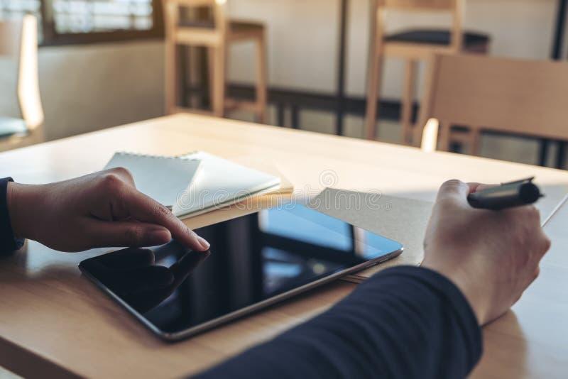 Las manos que señalan en una PC negra de la tableta defienden mientras que escriben en los cuadernos en oficina foto de archivo libre de regalías