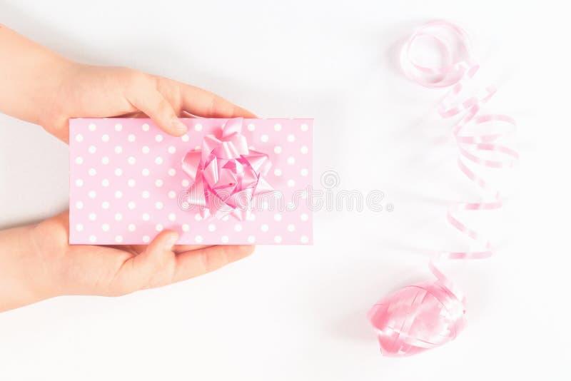 Las manos que sosten?an una caja de regalo rosada aislaron imágenes de archivo libres de regalías