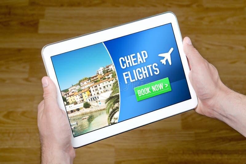 Las manos que sostienen la tableta con los flghts baratos para la venta añaden en Internet imagen de archivo