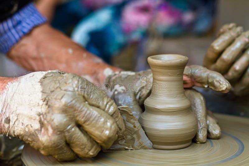 Las manos que trabajan en la cerámica ruedan, se cierran para arriba fotos de archivo libres de regalías