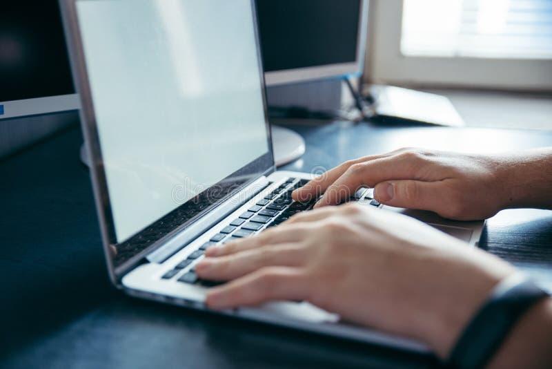 Las manos se cierran para arriba en el ordenador portátil foto de archivo