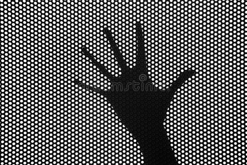 Las manos siluetean detrás de una rejilla foto de archivo libre de regalías