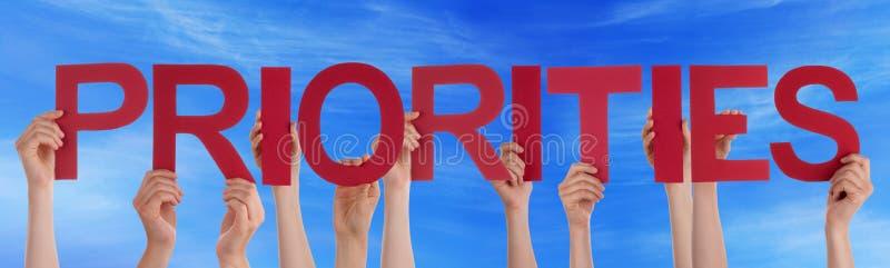 Las manos sostienen el cielo azul de las prioridades rectas rojas de la palabra foto de archivo libre de regalías