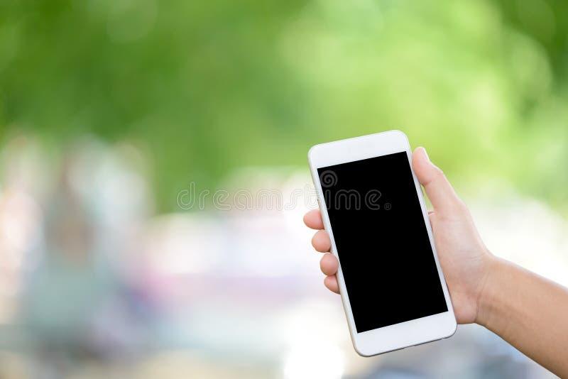 Las manos sostienen el teléfono elegante fotografía de archivo