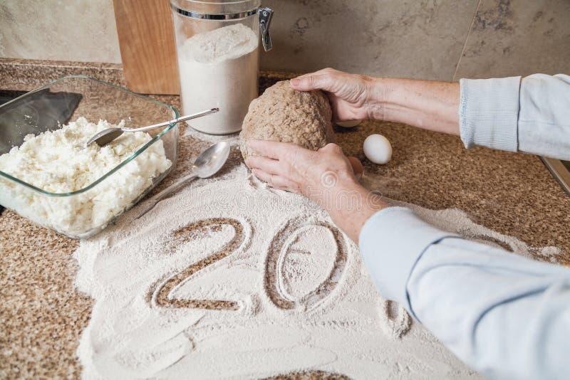 2019 las manos sostienen la pasta Mentira de la harina y de los huevos en el tablero de la mesa imagenes de archivo