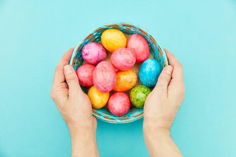 Las manos sostienen los huevos de Pascua en la cesta para pascua foto de archivo libre de regalías