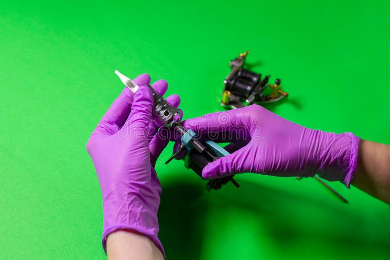 Las manos sostienen una máquina azul del tatuaje fotos de archivo libres de regalías