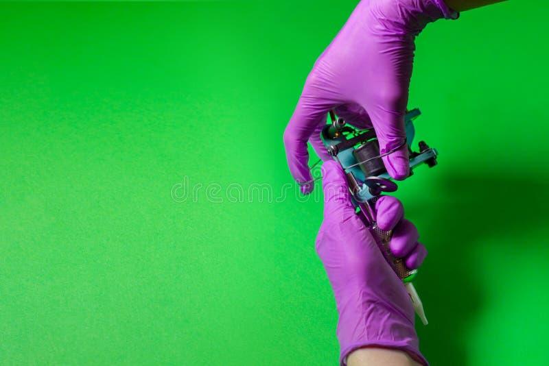Las manos sostienen una máquina azul del tatuaje imagenes de archivo
