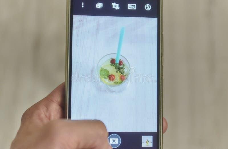 Las manos toman una imagen del cóctel del verano de su smartphone del teléfono móvil foto en la bebida del verano del teléfono ag imágenes de archivo libres de regalías