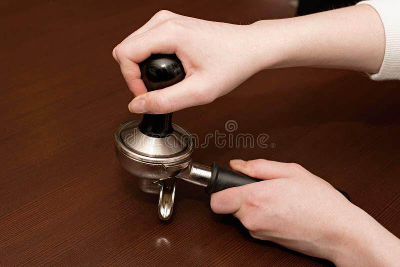 Las manos utilizan habas del café molido en tenedor imagen de archivo
