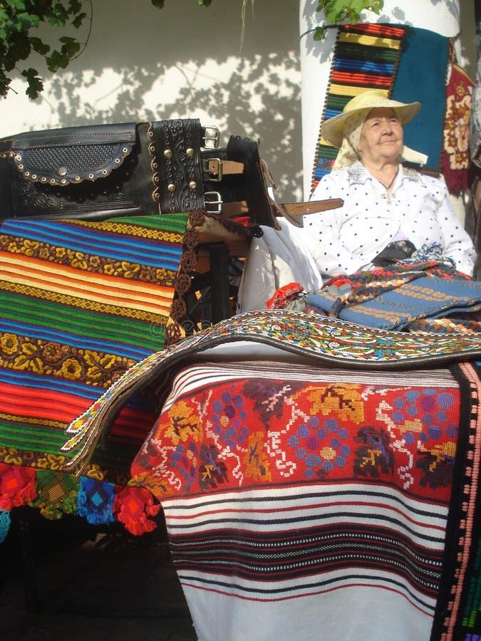 Las mantas tejidas tradicionales atascan en las mercancías tradicionales favorablemente en el museo campesino rumano en Bucarest, imagen de archivo libre de regalías