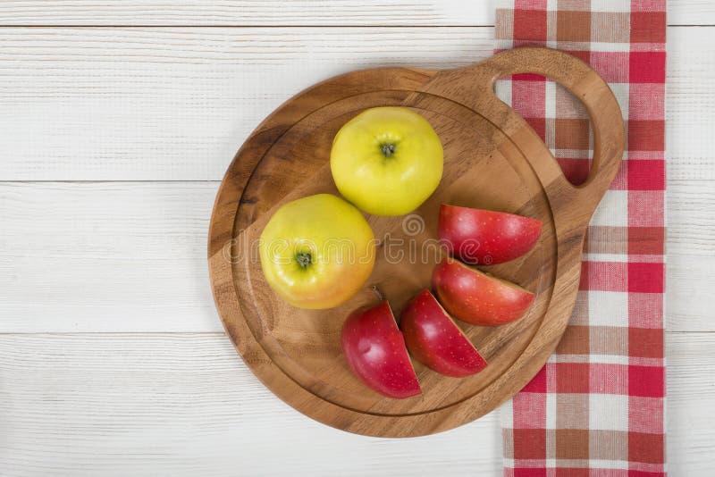 Las manzanas amarillas y rojas pusieron en un tablero de madera del corte fotografía de archivo libre de regalías