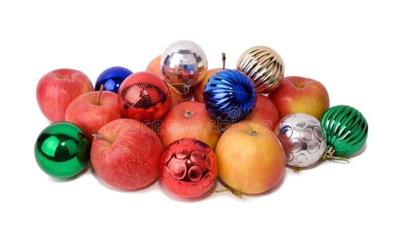 Las manzanas están entre bolas de la Navidad foto de archivo