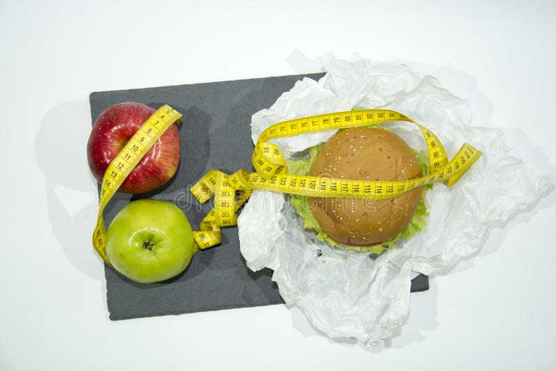 Las manzanas, la hamburguesa roja y verde y la cinta métrica mintiendo en una porción slate foto de archivo libre de regalías