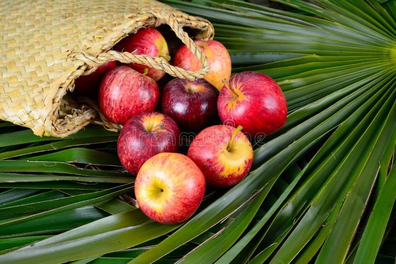 Las manzanas que se derraman fuera de un lino tejido mano empaquetan fotografía de archivo libre de regalías