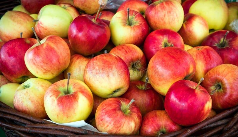 Las manzanas rojas jugosas frescas apilan en una cesta en venta Fondo natural hermoso imagenes de archivo