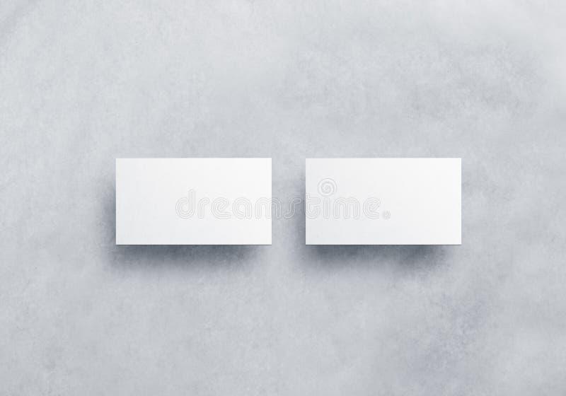 Las maquetas blancas en blanco de la tarjeta de visita aisladas en gris texturizaron el fondo fotos de archivo libres de regalías