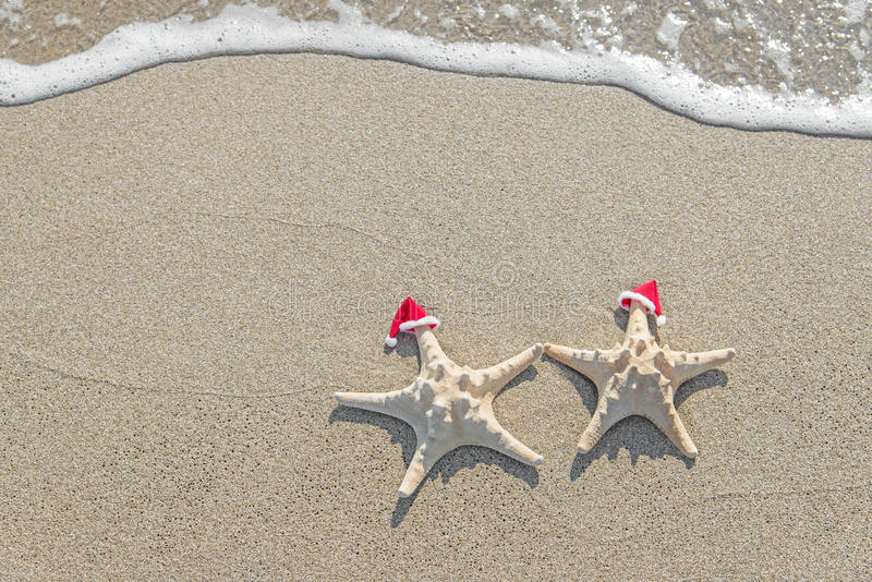 las Mar-estrellas se juntan en los sombreros de santa en la arena imagen de archivo libre de regalías