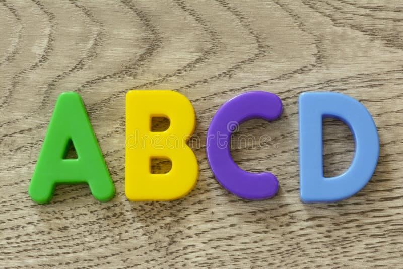 Las mayúsculas A B C D en letra plástica colorida plana juegan en fondo de madera gris imagen de archivo libre de regalías
