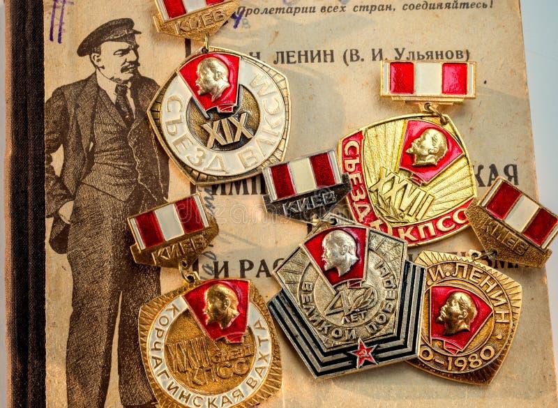 Las medallas soviéticas del jubileo que representaban a Lenin contra la perspectiva de los libros de segunda mano de Lenin imprim foto de archivo
