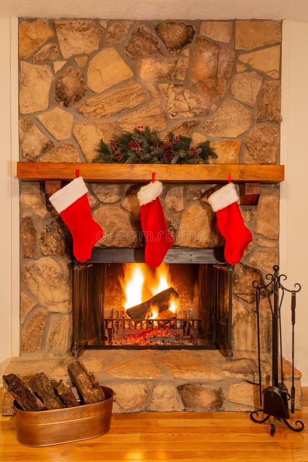 Las medias de la Navidad adornan una chimenea de piedra hermosa con un fuego que brilla intensamente foto de archivo