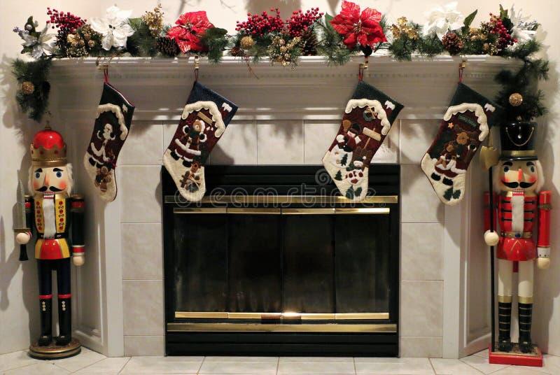 Las medias de la Navidad colgaron en la chimenea con los cascanueces que colocaban el reloj imagen de archivo