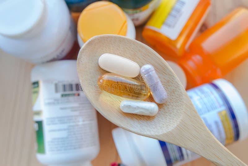 Las medicinas, los suplementos y las vitaminas están en una cuchara de madera imagen de archivo libre de regalías