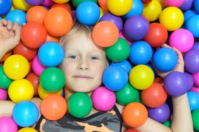 Las mentiras del muchacho, enterradas en las bolas coloridas del cuarto de juego imágenes de archivo libres de regalías