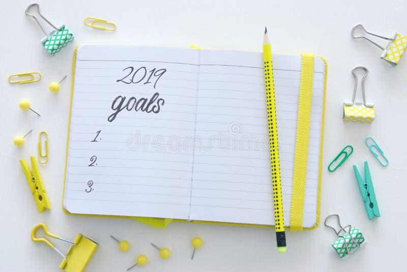 Las metas de la opinión de top 2019 enumeran con el cuaderno sobre el escritorio blanco de madera foto de archivo libre de regalías