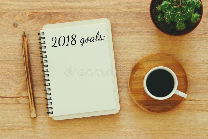 Las metas de la visión superior 2018 enumeran con el cuaderno, taza de café en el escritorio de madera foto de archivo
