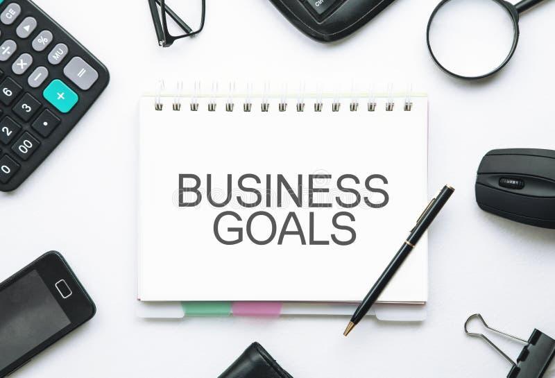 Las metas de negocio mandan un SMS en la libreta Concepto del asunto fotos de archivo