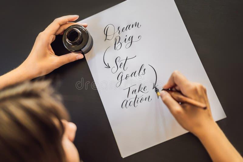 Las metas grandes ideales del sistema toman medidas El cal?grafo Young Woman escribe frase en el Libro Blanco Inscribiendo orname fotografía de archivo libre de regalías