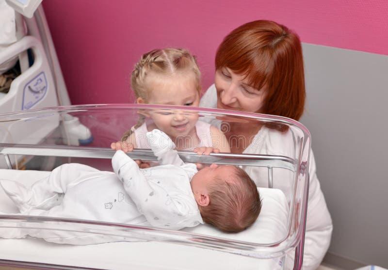 Las miradas de la hermana y de la abuela en un bebé recién nacido en el hospital fotos de archivo libres de regalías