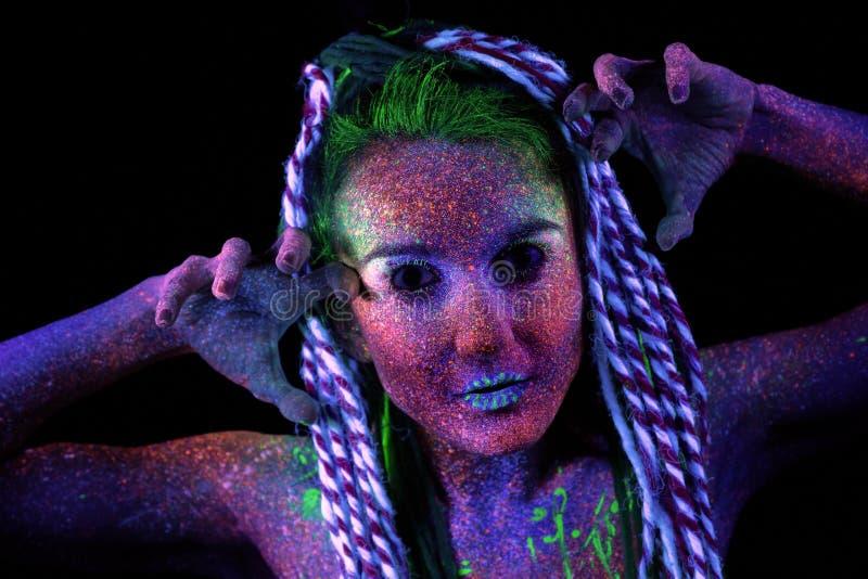 Las miradas de los extranjeros de la muchacha a la cámara encoge sus hombros, maquillaje ultravioleta Ella lleva a cabo sus manos foto de archivo libre de regalías